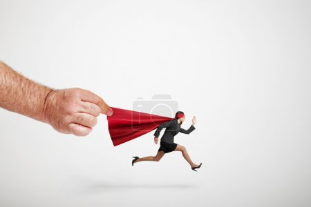 big mans hand holding the red cloak of running superwoman