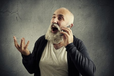 Photo for Emotional senior man talking on the phone and laughing over dark background - Royalty Free Image