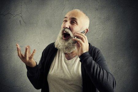 Photo pour Homme âgé émotionnel parlant au téléphone et riant sur fond sombre - image libre de droit