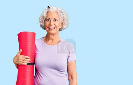 Senior grey-haired woman holding yoga mat looking ...