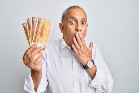 Photo pour Beau senior tenant 500 billets en couronne norvégienne couvrant la bouche à la main, choqué et effrayé par l'erreur. expression surprise - image libre de droit