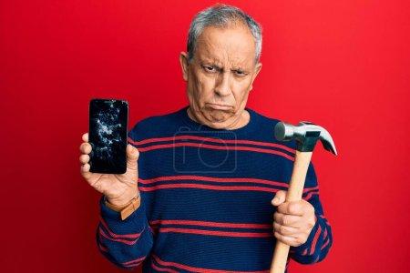 Photo pour Homme hispanique senior tenant smartphone cassé montrant écran fissuré et marteau sceptique et nerveux, fronçant les sourcils bouleversés en raison du problème. personne négative. - image libre de droit