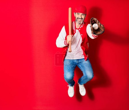 Photo for Middle age handsome man wearing sporty clothes smiling happy. Jumping with smile on face playing baseball using bat ,ball and glove over isolated red background - Royalty Free Image