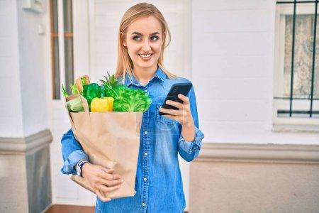 Photo pour Jeune fille blonde souriant heureux en utilisant un smartphone et tenant grocries sac en papier à la ville. - image libre de droit