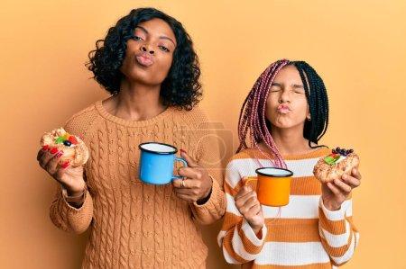Photo pour Belle mère et fille afro-américaine tenant des pâtisseries sucrées et buvant du café en regardant la caméra souffler un baiser étant belle et sexy. expression d'amour. - image libre de droit