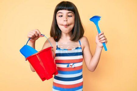 Kleines Mädchen mit Knall spielt mit Sommerschaufel und Eimerspielzeug und macht Fischgesicht mit Maul und schielenden Augen, verrückt und komisch.