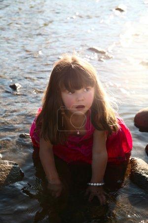 Photo pour Petite fille jouant dans un ruisseau d'eau peu profonde - image libre de droit