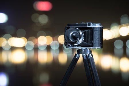 Retro camera the night view of city.