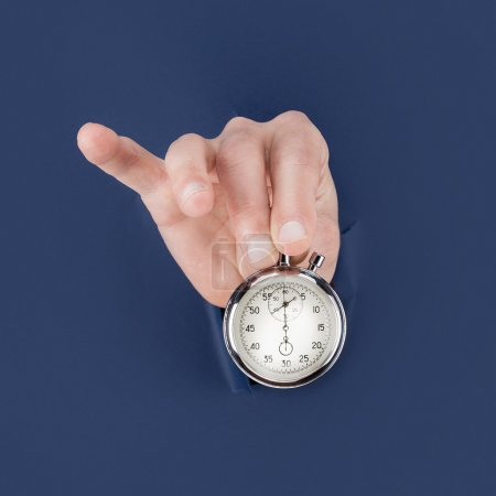 Male hand breaking through the blue paper background and holding antique clock