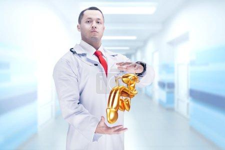Photo pour Docteur avec stéthoscope et pénis doré sur les mains dans un hôpital. Haute résolution . - image libre de droit