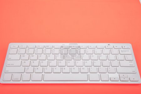 Computer keyboard on orange background