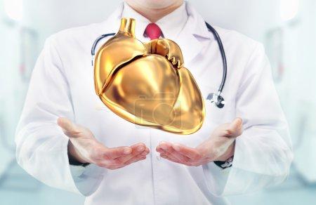 Photo pour Docteur avec stéthoscope et coeur doré sur les mains dans un hôpital. Haute résolution . - image libre de droit