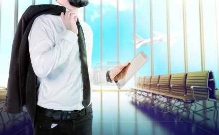 Businessman with digital tablet on blurred background airport.
