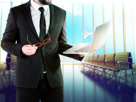 Businessman with digital notebook on blurred background airport.