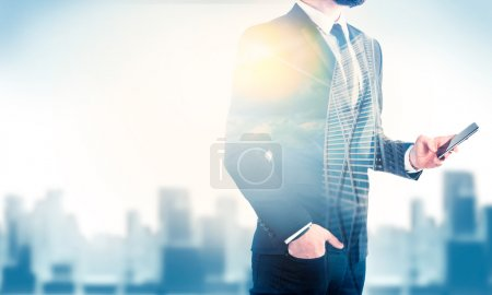 Double exposure of city and business man using mobile phone