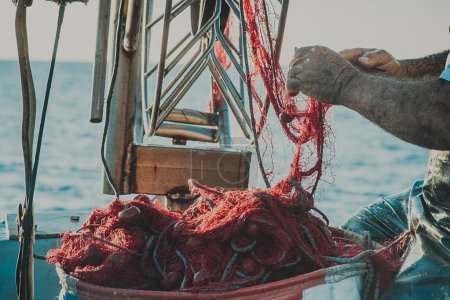 Bright orange fishing net with floats. Fisher boat in a sea. Hands of an old fisherman