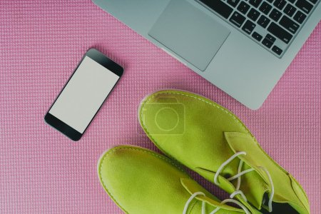 Green male shoes with laptop and mobile phone on pink background