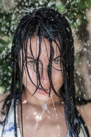Portrait of beautiful woman enjoying rain shower at sunny day