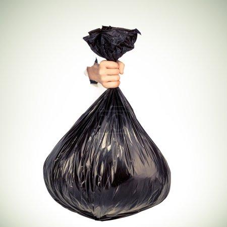 Hand holding black bag of rubbish. Studio shot.