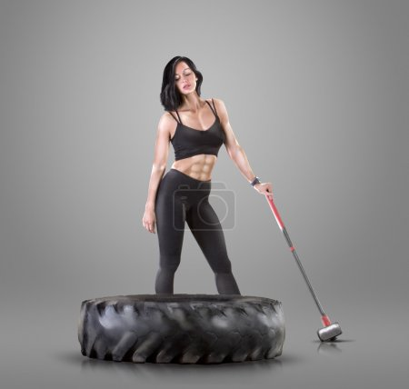Athletic young woman doing a fitness workout with hammer and tire on gray studio background