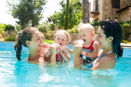 Two happy little girl with mothers in swimming pool