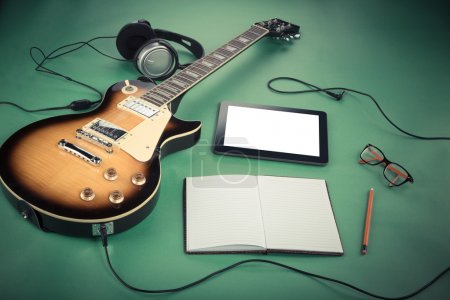 Electric guitar with notepad and old camera on green background