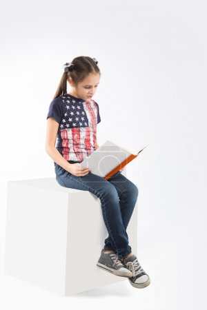 Little cheerful  girl with book on white background