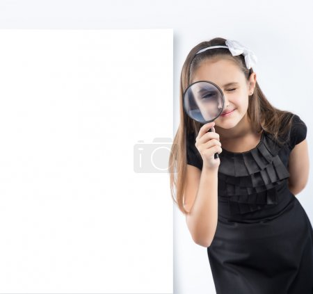 Cute  little girl looking through a magnifying glass. Educational concept