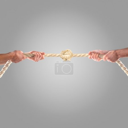 Hands of people pulling the rope on a gray background.  Competition concept