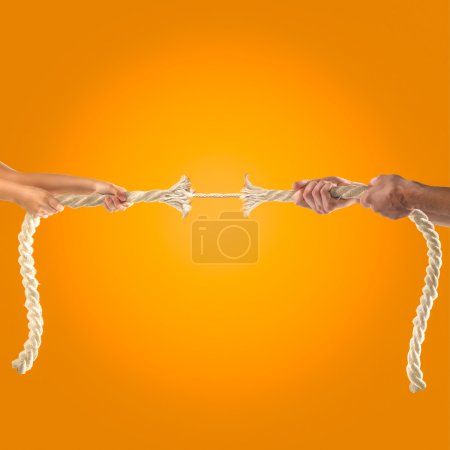 Hands of people pulling the rope on orange background. Competition concept