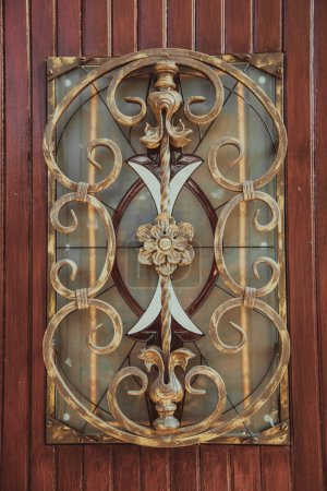 Ornate decorative wrought iron elements on the wood door