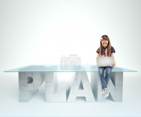 Cute little girl sitting on a PLAN table design, and holding a laptop. Bussines concept