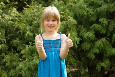 Girl 5 years old in blue dress shows thumbs