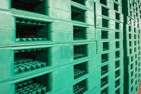 Green plastic pallets in warehouse.