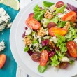 Fresh salad with nut grapes and blue cheese on whi...