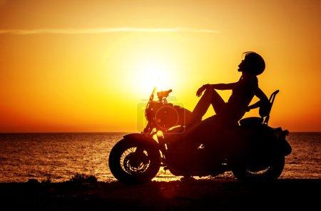 Photo pour Femme motard profitant du coucher du soleil, moto d'équitation féminine, conducteur de moto voyageant dans le monde entier, fille se reposant sur la route de la plage, mode de vie de liberté - image libre de droit