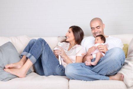 Foto de Los padres jóvenes con bebé en casa, sentado en el diván acogedor, familia disfrutando, amando a pareja con hija recién nacida, concepto de positividad y diversión - Imagen libre de derechos