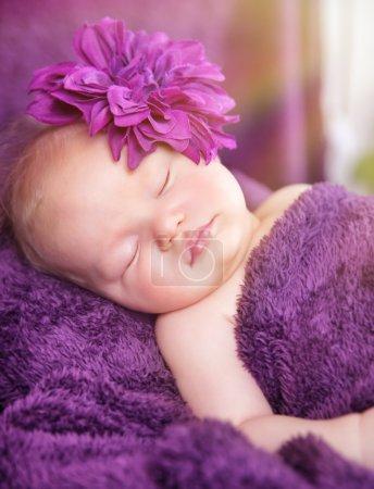 Photo pour Portrait de mignonne petite fille nouveau-née dormant à la maison, portant des accessoires de fleurs élégantes, la tendresse et le concept de mode bébé - image libre de droit
