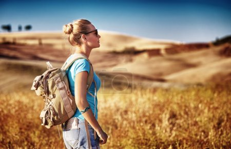 Photo for Tourist girl enjoying view of beautiful dry golden wheat hills, traveling along Europe in autumnal season, active lifestyle concept - Royalty Free Image