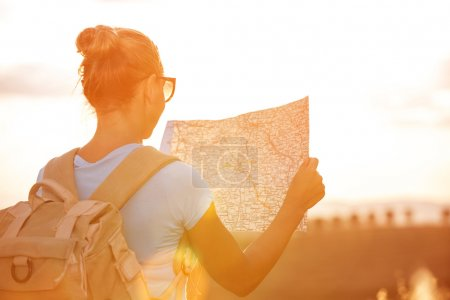 Photo for Back side of traveler girl searching right direction on map, bright orange sunset light, traveling along Europe, freedom and active lifestyle concept - Royalty Free Image