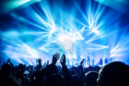 Photo pour Large group of happy people enjoying rock concert, clapping with raised up hands, blue lights from the stage, new year celebration concept - image libre de droit