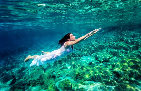 Photo pour Refreshing swimming underwater, beautiful young woman wearing fashion white long dress and dive into clear transparent sea, luxury summer vacation concept - image libre de droit
