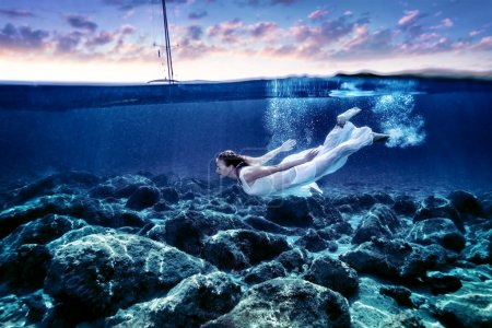 Photo pour Young woman diving in sunset time, enjoying swimming underwater, wearing long white dress, luxury summer vacation, freedom and pleasure concept - image libre de droit