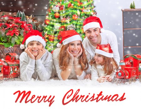 Photo for Cheerful parents with two cute smiling kids lying down near Christmas tree at home, festive greeting card with text space, happy family holiday concept - Royalty Free Image