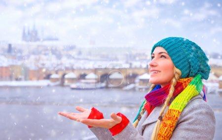 Photo pour Portrait of cute happy woman enjoy snowfall in beautiful Prague city, catches snowflakes by hands with pleasure, enjoying winter holidays - image libre de droit