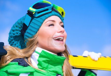 Photo for Closeup portrait of cute happy skier girl on blue sky background, extreme winter sport, active lifestyle concep - Royalty Free Image