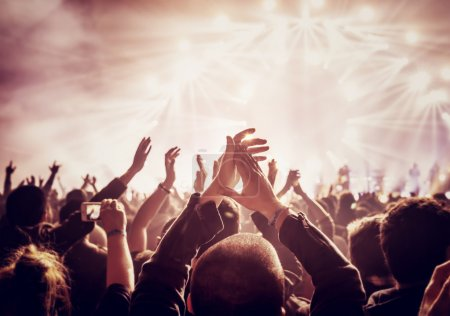 Photo for Vintage style photo of a crowd, happy people enjoying rock concert, raised up hands and clapping of pleasure, active night life concept - Royalty Free Image