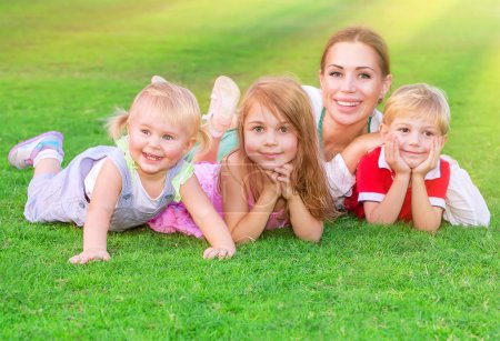 Photo for Happy big family having fun outdoors, young mother with three cute kids lying down on fresh green field, love and togetherness concept - Royalty Free Image