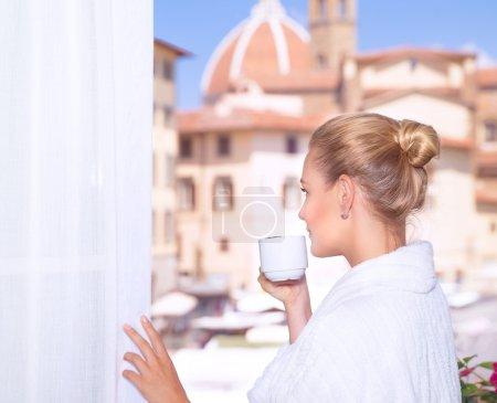 Drinking coffee near by window