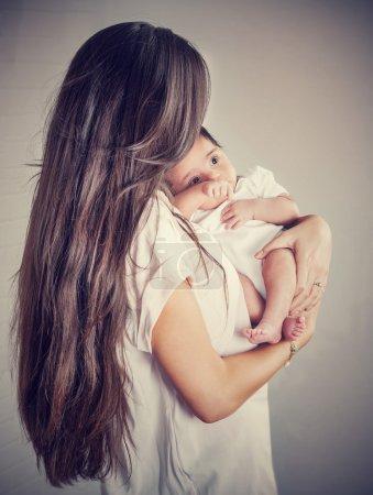 Photo pour Mère douce avec petit bébé isolé sur fond gris, femme aux cheveux longs foncés tenant sa précieuse fille nouveau-née, amour et concept de maternité heureuse - image libre de droit